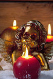 Golden putto with burning candles on pile of snow Stock Photos
