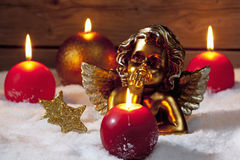 Golden putto with burning candles and star shaped christmas decorations on pile of snow Stock Image