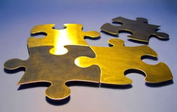 Golden puzzle pieces. Four gold coloured puzzle pieces on blue-grey background royalty free stock photography