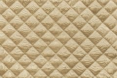 Golden quilted fabric with grained texture Stock Photos
