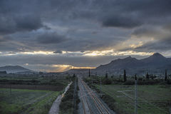 Golden rails. Straight rail track under the morning cloudy sky, while the sun rays appear towards all directions Stock Photos