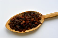 Golden raisins in wooden spoon on white background Royalty Free Stock Photo