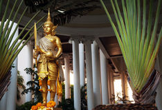 Golden Rama statue wearing traditional costume. Gold Hindu god sculpture holding sword and cloth sack Stock Image