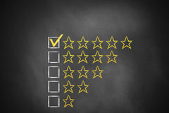 Golden rating stars chalkboard. Golden rating stars on black chalkboard royalty free stock images