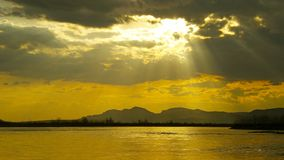 The golden ray of the sun from behind a dark cloud illuminates the evening lake. It symbolizes a ray of hope in the twilight, the belief that everything will stock images