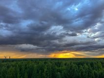 Golden rays of sunset. Sunset view with low blue and grey spring cloudy skies to Yunyolovskiy reserve royalty free stock photography