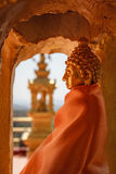 Golden recess with elegant gold Buddha statue draped with the orange buddhist robe Royalty Free Stock Photo