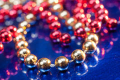 Golden and red beads on blue background Stock Images