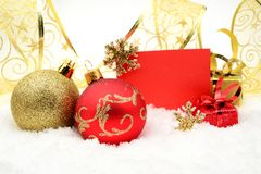 Golden and red christmas decoration on snow with wishes card Stock Image