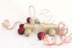 Golden and red Christmas gift. Gift wrapped with golden paper and red and golden ribbons. The gift is surrounded by gold and red Christmas ornaments on a white Royalty Free Stock Images
