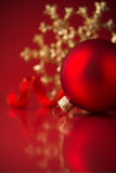 Golden and red christmas ornaments on red background. With copy space Stock Images
