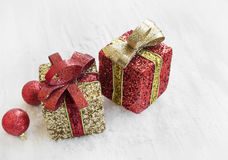 Golden and Red Christmas Presents and Balls in the Snow. Festive Red and Golden Christmas Presents and Balls with Glitter in the Snow Royalty Free Stock Image