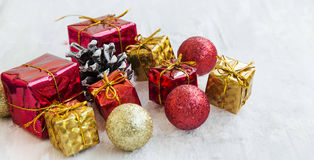 Golden and Red Christmas Presents and Balls in the Snow. Festive Red and Golden Christmas Presents and Balls with Glitter in the Snow Stock Image