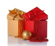 Golden and red classic gift boxes with satin bows, beaded garlands and glass christmas ball. Isolated on white background Stock Photos