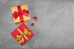 Golden and red classic shiny gift boxes with satin bows and small hearts. On gray concrete background Royalty Free Stock Photography