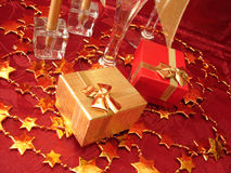 Golden and red gift boxes, stars on beautiful background with ch. Ampagne glasses Stock Photography