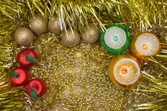 Golden, red, green and yellow New Year or Christmas baubles on golden base with golden ragged decoration. royalty free stock photography