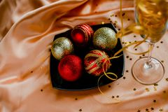 Golden and Red New Year Decorations Christmas balls. New Year Decorations Christmas balls, red and golden on golden background with stars and black plate royalty free stock images