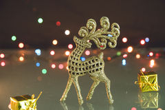 Golden reindeer and small gifts on Christmas background with bokeh lights.  Royalty Free Stock Images