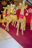 Golden reindeers near Christmas tree and gifts Royalty Free Stock Photography