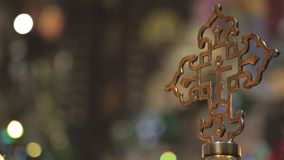 Golden religious cross on background of the lights in church. Christian symbol of faith filled with precious metal with patterns stock footage