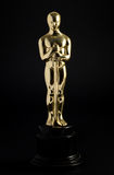 Golden replica of an Oscar. Film award on a black background royalty free stock photo