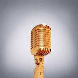 Golden retro microphone on grey background. Stock Photos