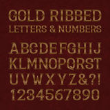 Golden ribbed letters and numbers with flourishes on red marble Royalty Free Stock Image