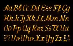 Golden ribbon alphabet letters on black background Stock Photos