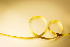 Golden ribbon. On golden background Royalty Free Stock Images