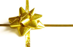 Golden ribbon and bow. Gold ribbon and bow of a present isolated on white stock image