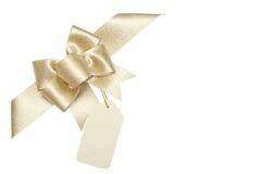 Golden ribbon bow with blank gift tag Stock Photography