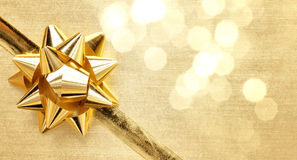 Golden ribbon bow with bokeh Stock Images