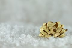 Golden ribbon bow. For Christmas gift wrapping on white snow surface Royalty Free Stock Image