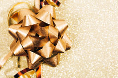 Golden ribbon bow with little sparkles in bokeh Royalty Free Stock Photography
