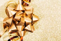 Golden ribbon bow with little sparkles in bokeh royalty free stock images