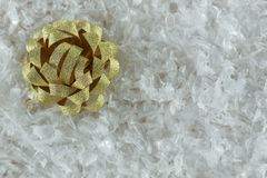 Golden ribbon bow in snow. Golden ribbon bow for Christmas gift wrapping on white snow surface. Top view Stock Image