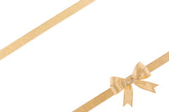 Golden ribbon with a bow. On white background Royalty Free Stock Photos