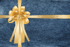 Golden ribbon and bow, wrap on blue denim jeans texture gift box background Stock Images