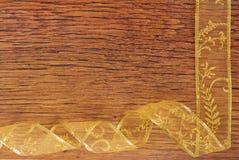 Golden ribbon frame  on wood Royalty Free Stock Photos