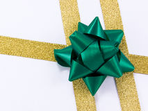 Golden ribbon with green bow. Christmas decoration golden ribbon with green bow isolated on white Royalty Free Stock Image