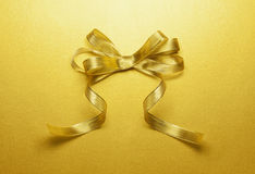 Golden ribbon tied in a bow. On the golden paper Stock Photos