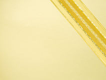 Golden ribbon on yellow space Royalty Free Stock Photos