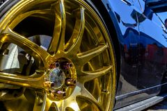 Golden rims on a black car looking very reflective. Various tires at a southern California event Stock Photography