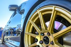 Golden rims with reflective black car and break pads showing thr. Ough the spokes. Orange county Subifest photos over summer 2017 Stock Image