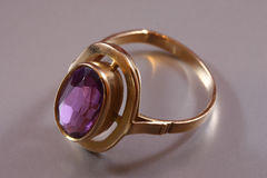 Golden ring. With purple stone on the gray background Stock Photography