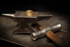 Golden ring on an anvil and a goldsmith hammer in the jewelry wo. Rkshop, still life with copy space in the dark background, selected focus, narrow depth of Royalty Free Stock Photo