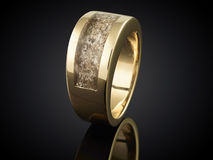 Golden ring with ashes  on black Stock Image