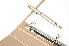 Golden ring binder and pen Stock Image