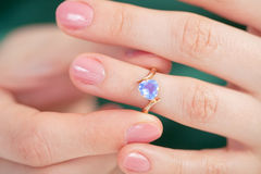 Golden ring with blue jewel try on a finger Stock Photos